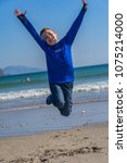 a small boy jumps on the beach  ... | Shutterstock . vector #1075214000