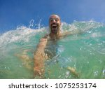 man having fun with waves at... | Shutterstock . vector #1075253174
