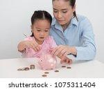mother teach her kid to saving... | Shutterstock . vector #1075311404