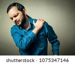man has the shoulder pain | Shutterstock . vector #1075347146