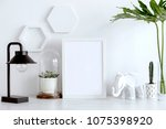 Small photo of Stylish scandinavian interior with white mock up frame, lamp, cacti, leafs and white hexagone shapes. Concept of modern space.