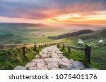 morning sun casting golden... | Shutterstock . vector #1075401176