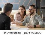 Small photo of Happy millennial couple getting keys to new home from realtor, customers renters tenants make deal buying renting house at meeting with agent, mortgage loan investment, real estate ownership concept