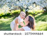 happy mom  holding her cute... | Shutterstock . vector #1075444664