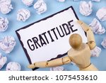 Small photo of Handwriting text writing Gratitude. Concept meaning Quality of being thankful Appreciation Thankfulness Acknowledge written on Sticky note paper within Paper Balls on Plain background Wooden Toy