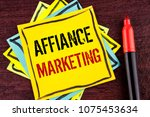 Small photo of Handwriting text Affiance Marketing. Concept meaning joining two or more companies in same field mutual goal written on Yellow Sticky note paper on wooden background Marker next to it.