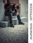 young depressed man sitting in... | Shutterstock . vector #1075522226
