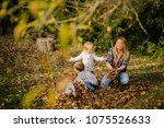 Family Playing In Autumn Leaf...
