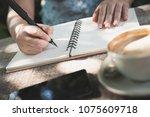 woman hand writing on notenook... | Shutterstock . vector #1075609718