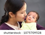 cheerful young mother holding... | Shutterstock . vector #1075709528