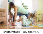 young mother playing twister... | Shutterstock . vector #1075864973