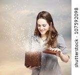 Happy Young Woman Opening a Gift Box - stock photo