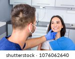a young dentist treating a... | Shutterstock . vector #1076062640
