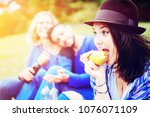 young woman eating a pear and... | Shutterstock . vector #1076071109