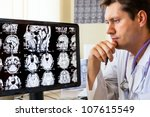 Stock photo doctor in hospital looking at ct scan 107615549