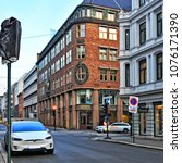 Small photo of Tesla car in Oslo downtown. Modern urban landscape. Residential houses. Norwegian architecture. Accommodation and life in North Europe. Norway, Oslo - November 4, 2017