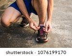 male runner tying running shoes ...   Shutterstock . vector #1076199170