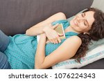 beautiful woman laying on home... | Shutterstock . vector #1076224343