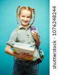 Small photo of Young smiling schoolchild with backpack on her shoulders and notebooks in hands stands on isolated blue background, has good mood, wears school uniform. Schoolgirl going to school.