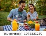 young couple enjoying food... | Shutterstock . vector #1076331290