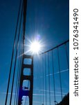 Small photo of Golden Gate bridge against a high noon sun, silhouette