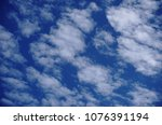 Small photo of Cirrocumulus and Altocumulus fluffy clouds on light blue sky background.