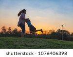 silhouette of a happy little... | Shutterstock . vector #1076406398