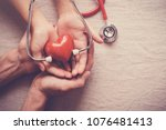 child and adult holding red... | Shutterstock . vector #1076481413