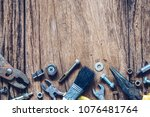 Small photo of Variety Handy Tools on grunge wooden background. Top view close up of wrenches, Pliers, screwdriver, nuts and bolts on wood background with copy space for your text. Worker's, Labor's day background.