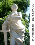 Small photo of justice allegory white marble statue of woman with sword at summer garden, Saint Petersburg, Russia