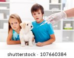 Vaccination for pets - worried kids with their dog at the veterinary doctor - stock photo
