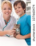 Boy and his kitten at the veterinary doctor office-focus on the cat - stock photo