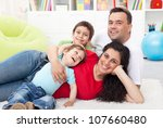 Happy young family with two small kids together at home - stock photo
