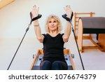 pilates reformer eldery blond... | Shutterstock . vector #1076674379