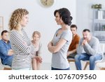 Small photo of Two happy women making amends during a group psychotherapy meeting