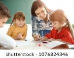 female teacher helping girl...   Shutterstock . vector #1076824346