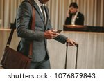 Stock photo cropped shot of businessman in hotel lobby with mobile phone and luggage male business traveler 1076879843