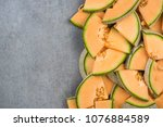 Cantaloupe melon slices, food border background, top view.