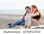 two girls are siting on the... | Shutterstock . vector #1076911553