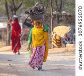 Small photo of DAHMI KALAN - INDIA, JANUARY 13, 2018: Indian woman in colorful dress carrying woods on the head in small village in Dahmi Kalan region near Jaipur in Rajasthan.