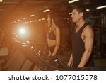 slim woman and muscular male... | Shutterstock . vector #1077015578
