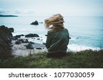 girl sitting on a cliff... | Shutterstock . vector #1077030059