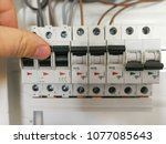 Male finger switching circuit brakers inside electrical panel cabinet - stock photo