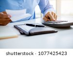 woman with bills and calculator.... | Shutterstock . vector #1077425423