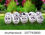 Garden party and many white eggs with funny faces - stock photo