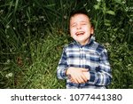 boy laughing lying in the grass.   Shutterstock . vector #1077441380