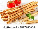 Bunch of grissini breadsticks with tomatoes on white background