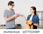 teenager giving book to boy at... | Shutterstock . vector #1077510389