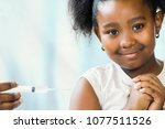 Small photo of Brave little ponytailed african girl receiving protective disease vaccine.Hand holding syringe with needle near upper arm.