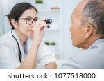 asian doctor woman examine eyes ... | Shutterstock . vector #1077518000